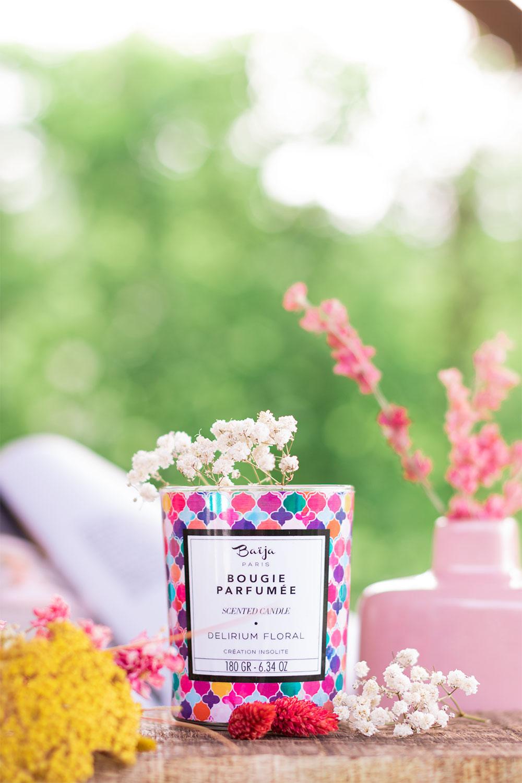 La bougie Delirium Floral de Baïja sur une planche en bois brut au milieu de fleurs séchées roses et blanches