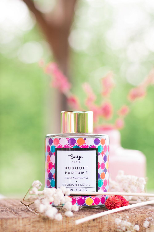 Le bouquet parfumé Delirium Floral de la marque Baïja sur une planche en bois avec des fleurs séchées roses et blanches