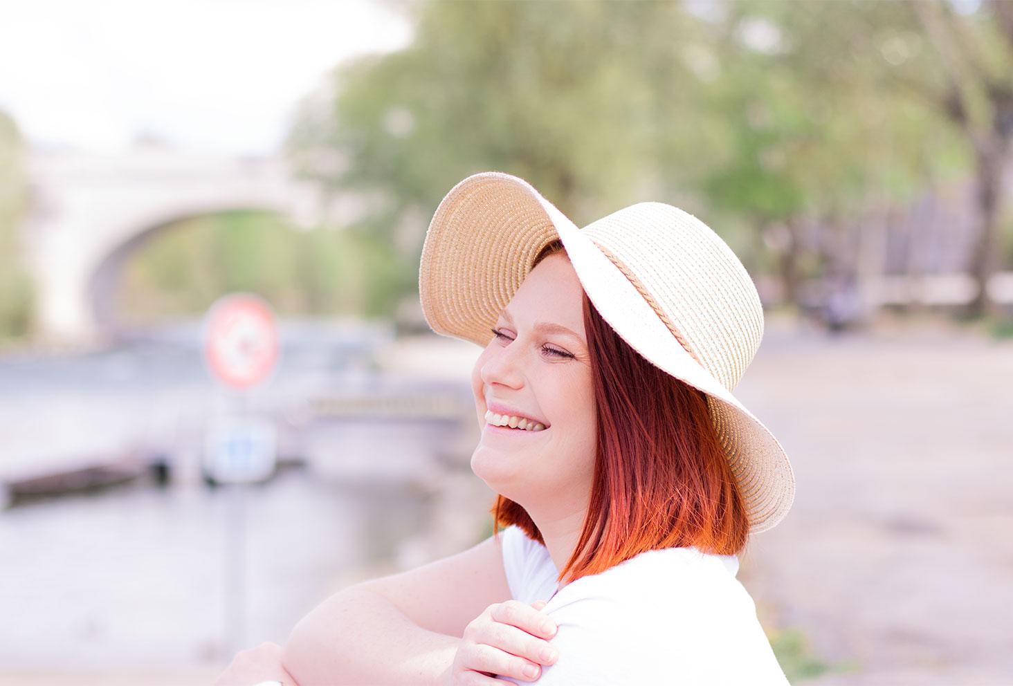 Zoom sur le chapeau de paille porté, avec le sourire, de profil sur les bords de Loire