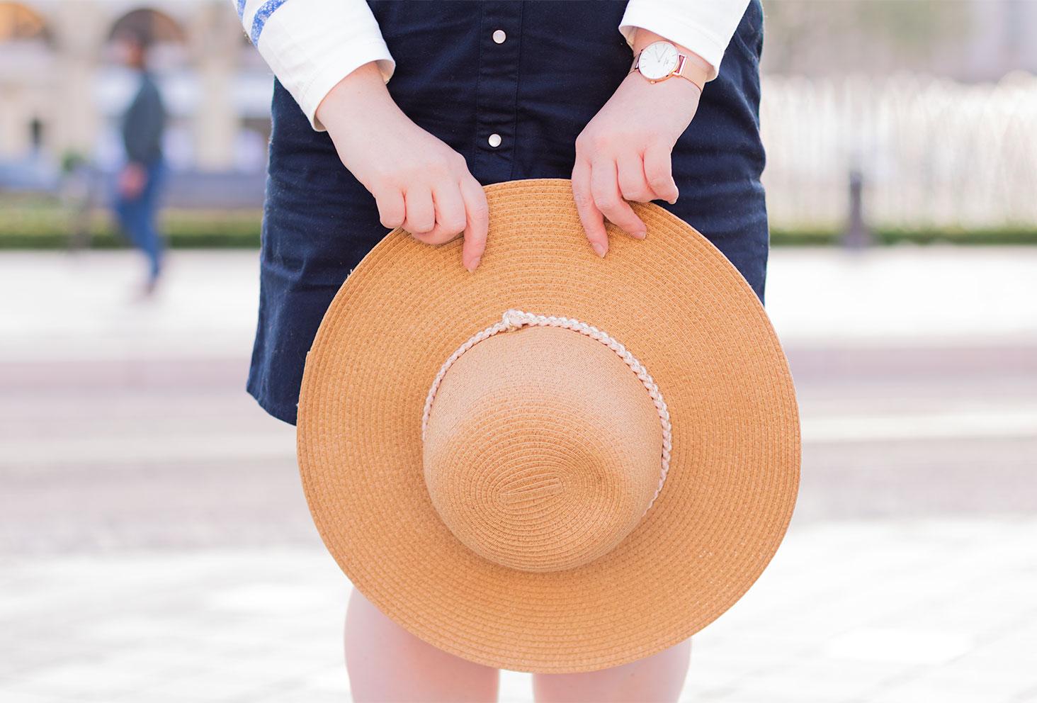 Zoom sur un chapeau en paille tenue entre les mains