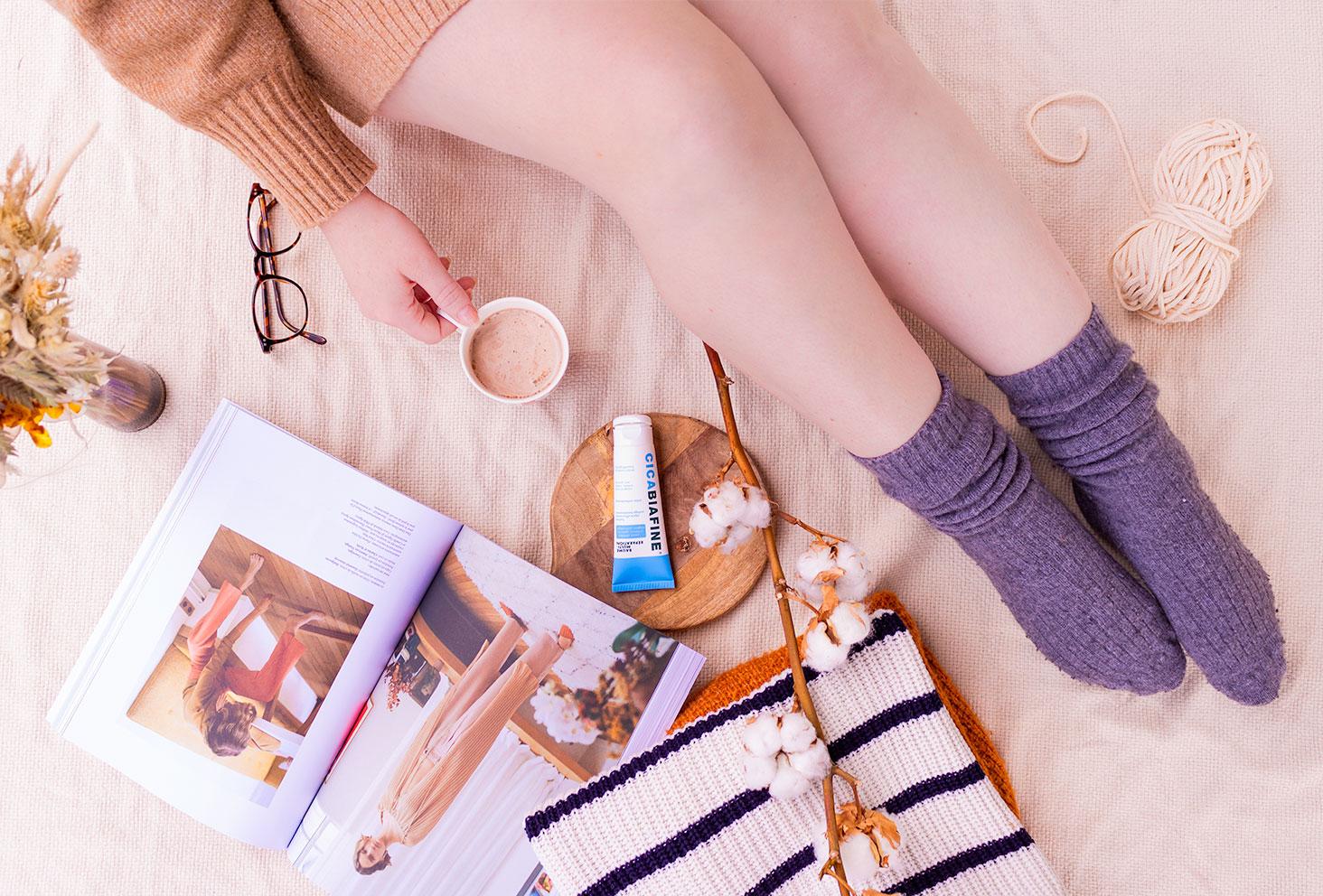 Moment cocooning sur un plaid en chaussette et gros pull, une tasse de café à la main et un magazine ouvert, avec le baume multi-réparation de Cicabiafine