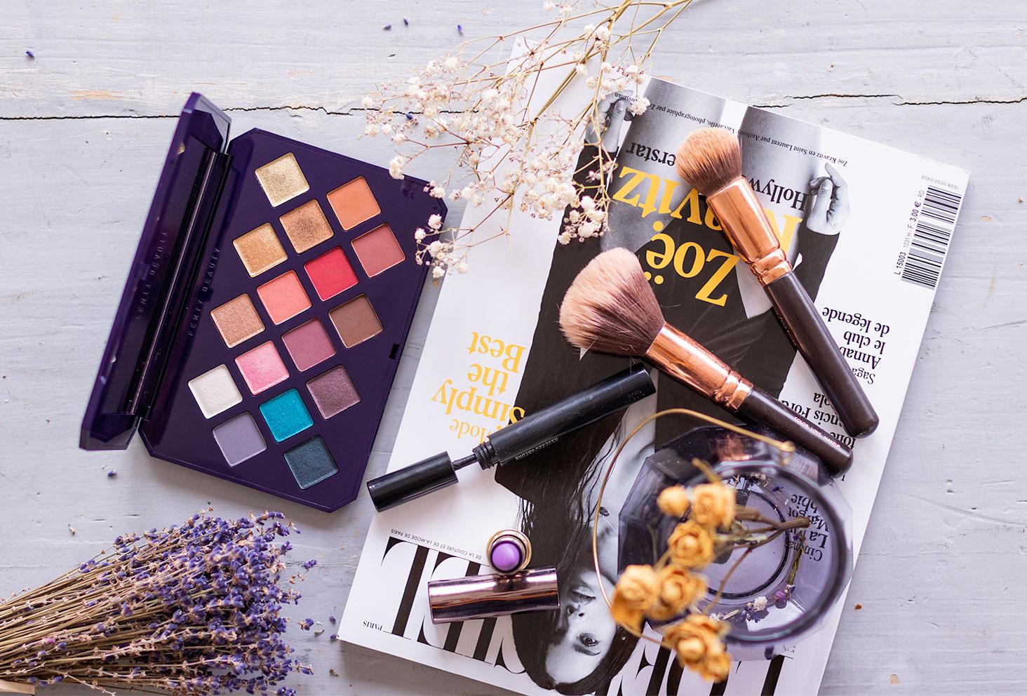 La palette Moroccan Spice de Fenty Beauty by Rihanna posée sur une table en bois gris, à coté de maquillage et d'un magazine, avec des fleurs séchées violettes et blanches