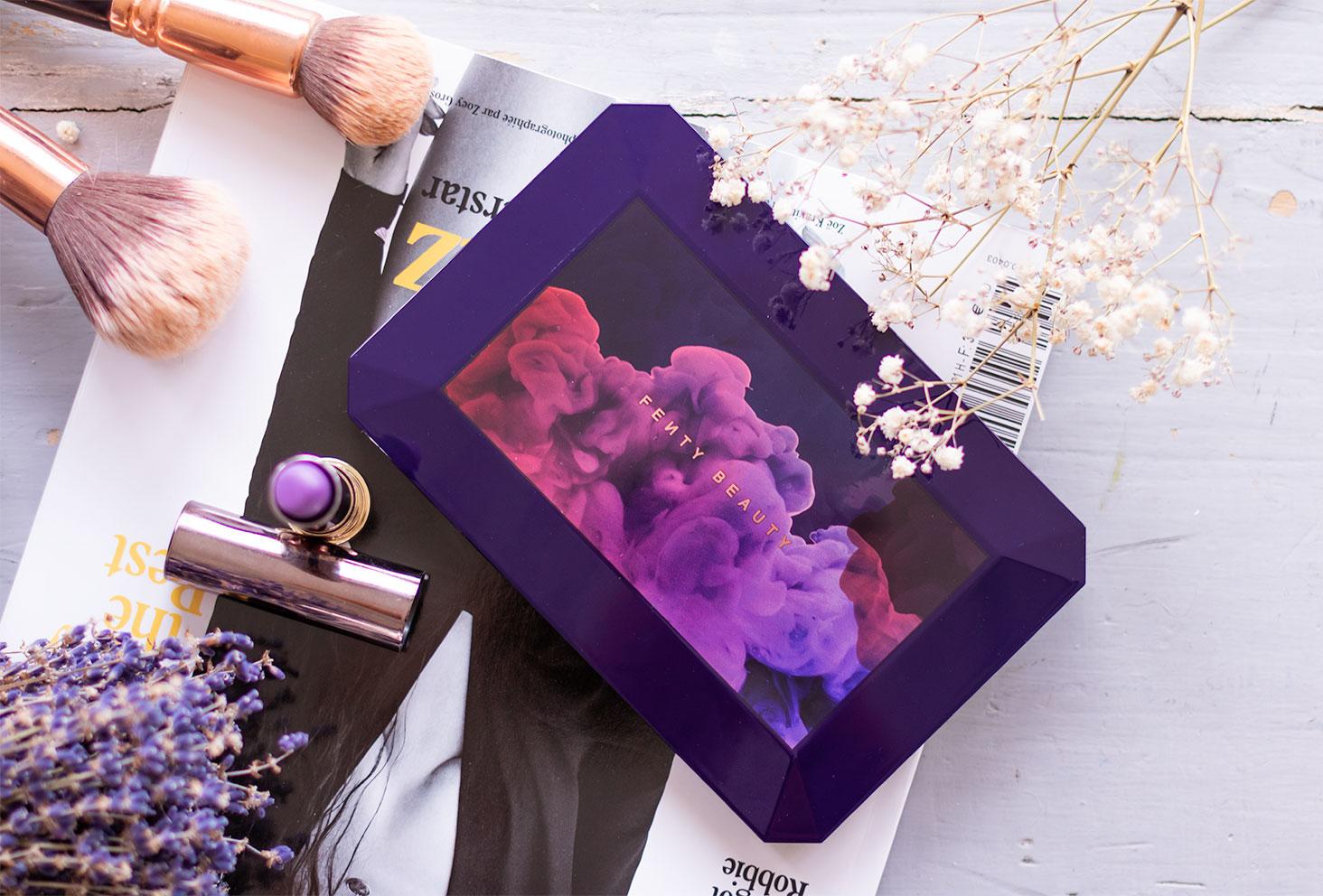Zoom sur le packaging de la palette Moroccan Spice de Fenty Beauty fermé, sur un magazine au milieu de maquillage et de fleurs sèches