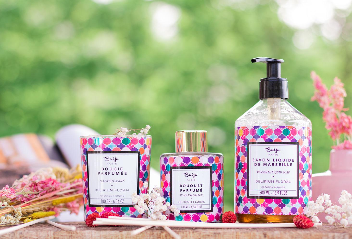Zoom sur le savon liquide de Marseille, la bougie et le bouquet parfumé de la gamme Delirium Floral de Baïja, posés sur une planche en bois devant un magasine, entourés de fleurs séchées