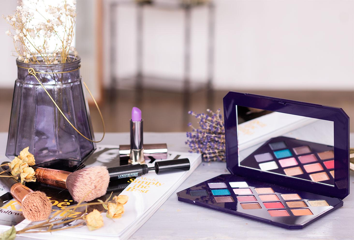 La palette Moroccan Spice de Fenty Beauty by Rihanna posée sur une table à côté d'un magazine beauté, entourée de maquillage et de fleurs séchées