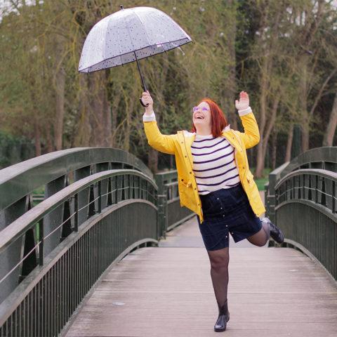 Sous la pluie, le parapluie dans les airs, en ciré jaune et bottes de pluie