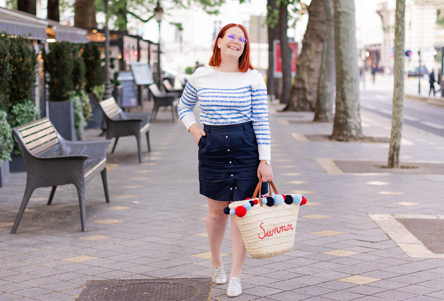 Dans la rue près des restaurants de la place Jean Jaurès, avec le sourire, en marinière Le Lucien et panier en paille Summer dans la main
