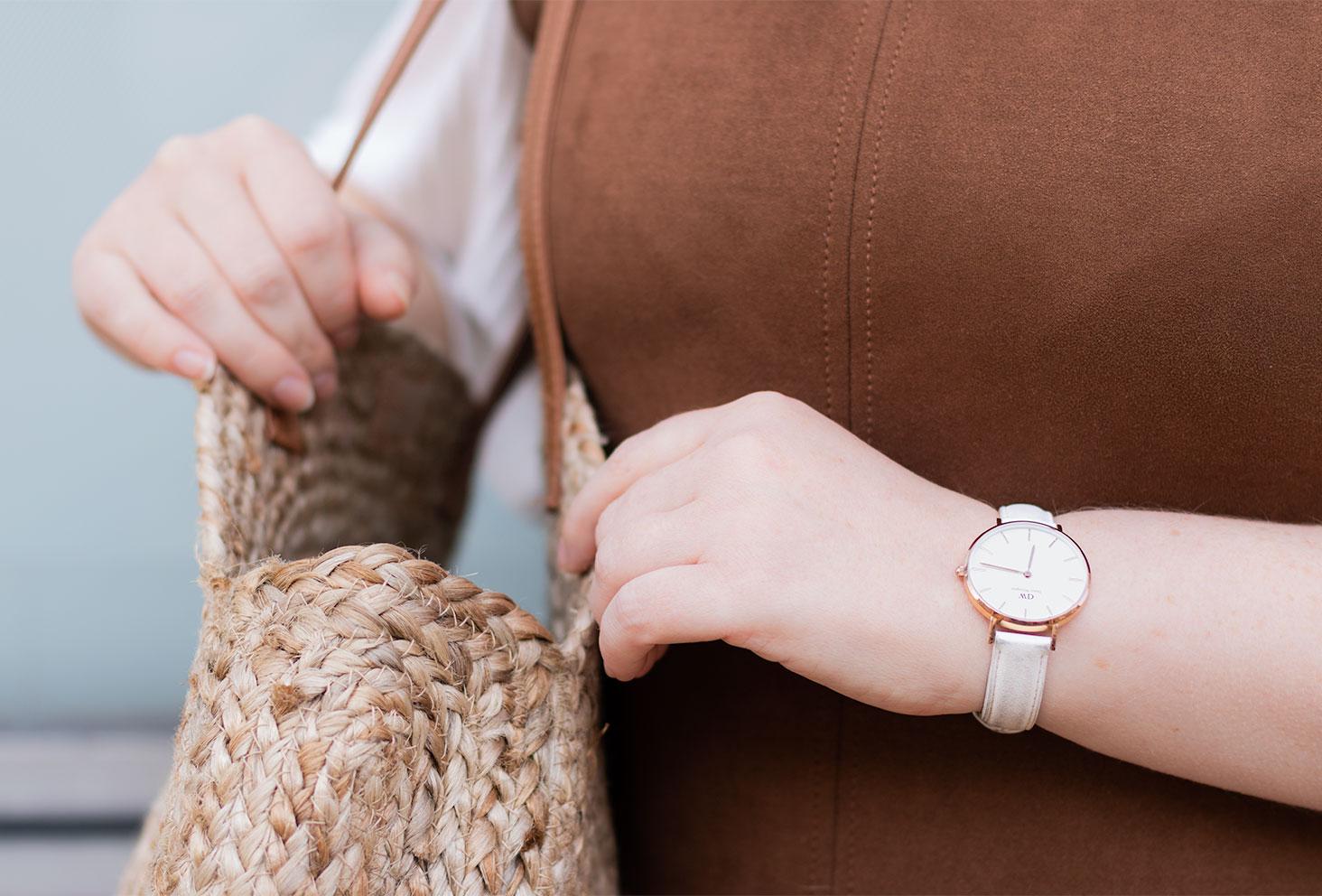 La montre blanche portée, en train de chercher dans un sac en paille à l'épaule