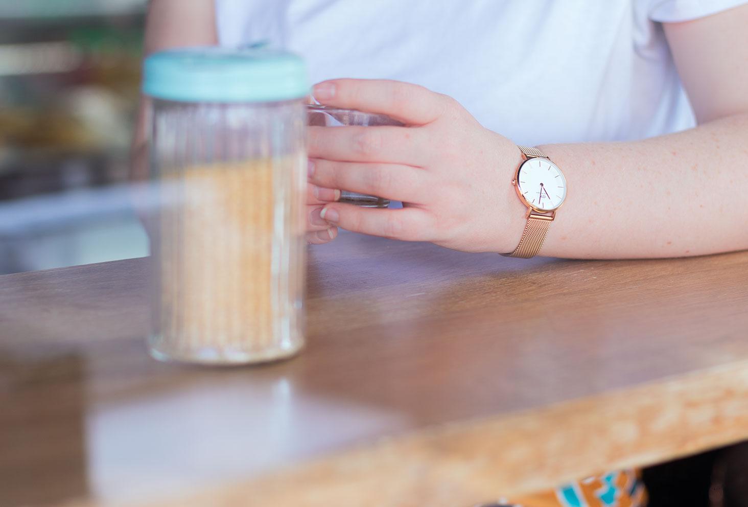 Zoom sur la montre dorée portée, un café dans la main, accoudé sur un bar dans un café de Tours