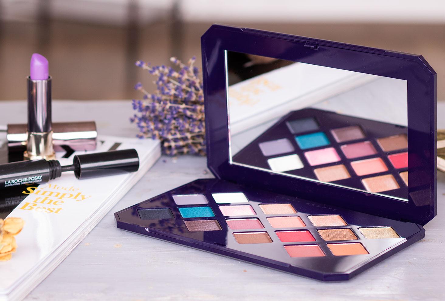 Zoom sur la palette Moroccan Spice de Fenty Beauty by Rihanna posée sur une table à côté d'un magazine beauté, entourée de maquillage et de fleurs séchées violettes