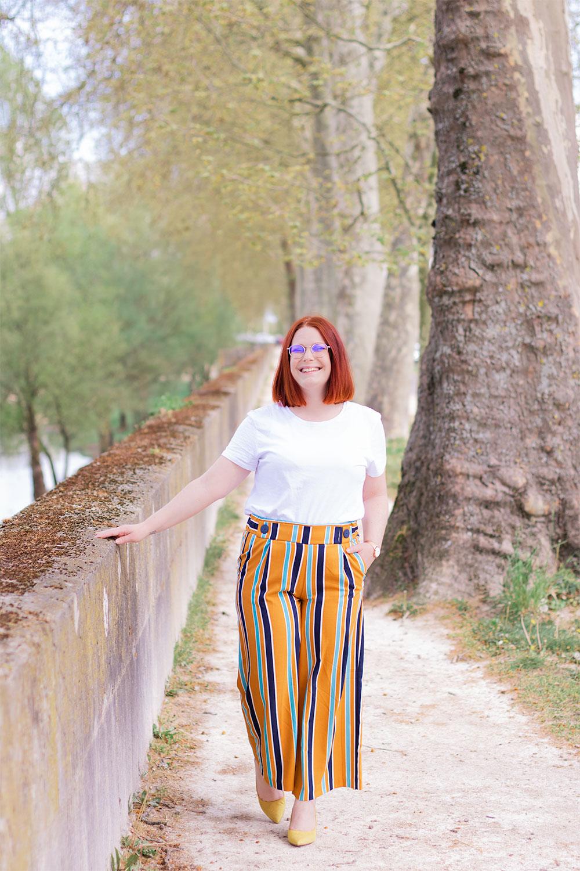 Dans un chemin sur les bords de la Loire, en pantalon fluide à rayures bleues et jaunes, avec le sourire une main dans la poche et l'autre sur le mur