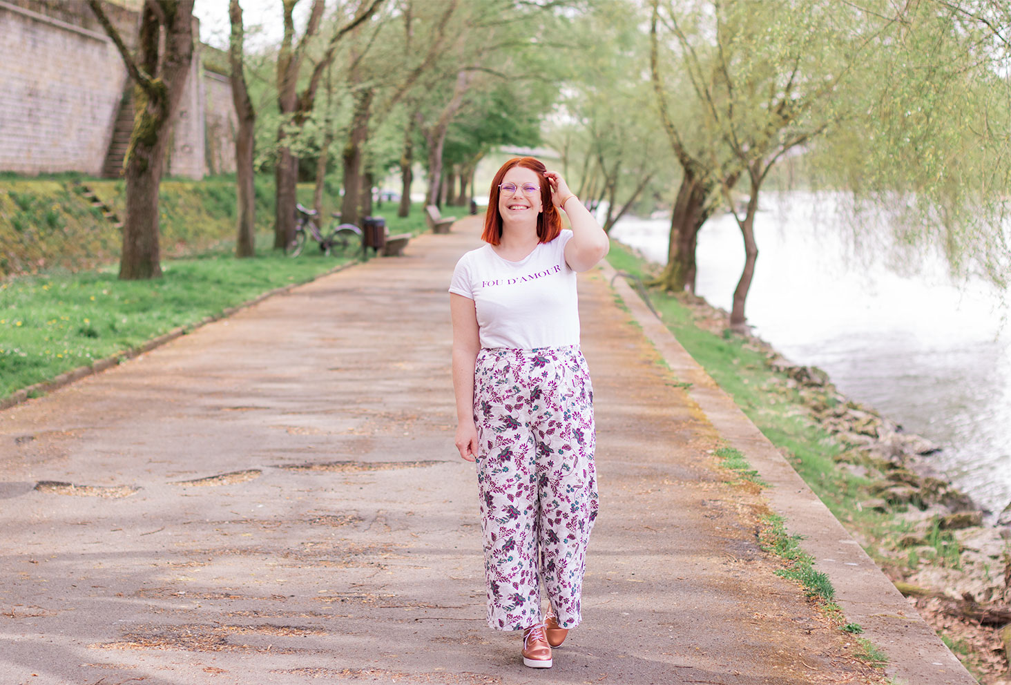 """Sur les bords de Loire, une main dans les cheveux, en pantalon fluide blanc à fleurs violettes et t-shirt """"Fou D'amour"""""""
