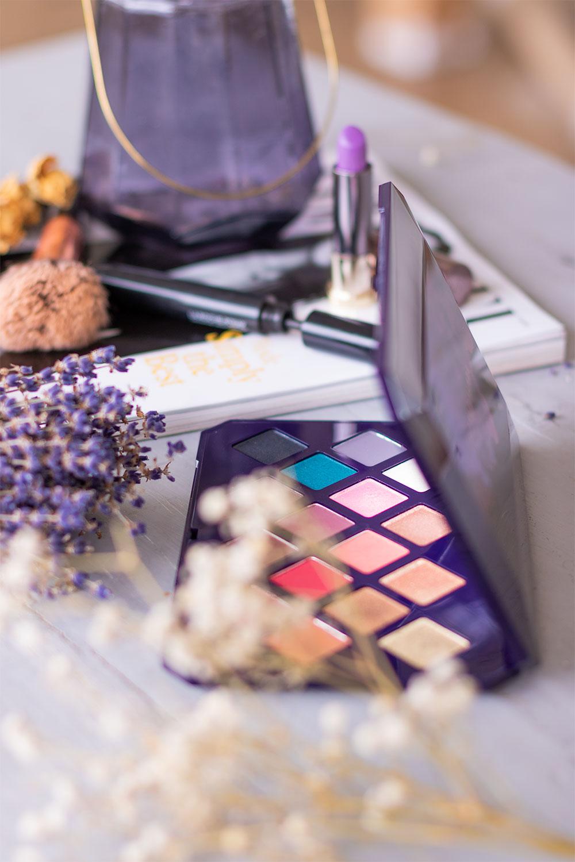 La palette Moroccan Spice de Fenty Beauty cachée derrière des fleurs séchées blanches, posée sur une table grise en bois devant un magazine