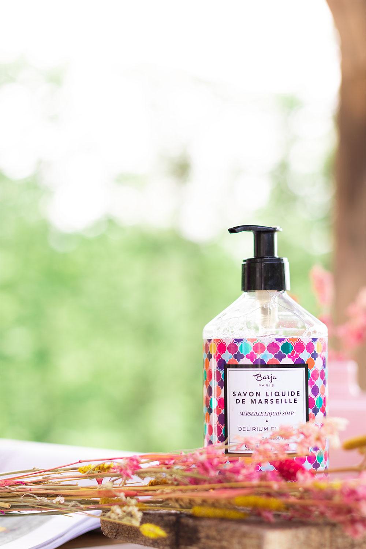 Le savon liquide de Marseille de la gamme Delirium Floral de Baïja sur une planche en bois caché derrière un bouquet de fleurs séchées