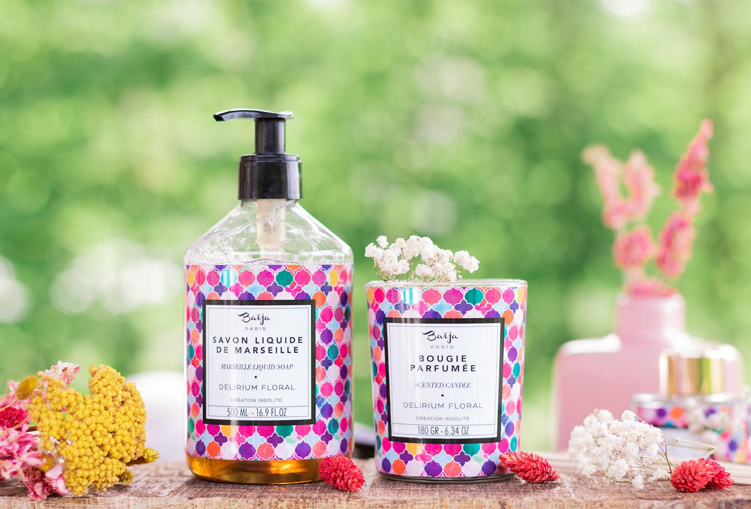 Le savon liquide de Marseille et la bougie parfumée Delirium Floral de la marque Baïja sur une planche en bois au milieu de bouquets de fleurs séchées