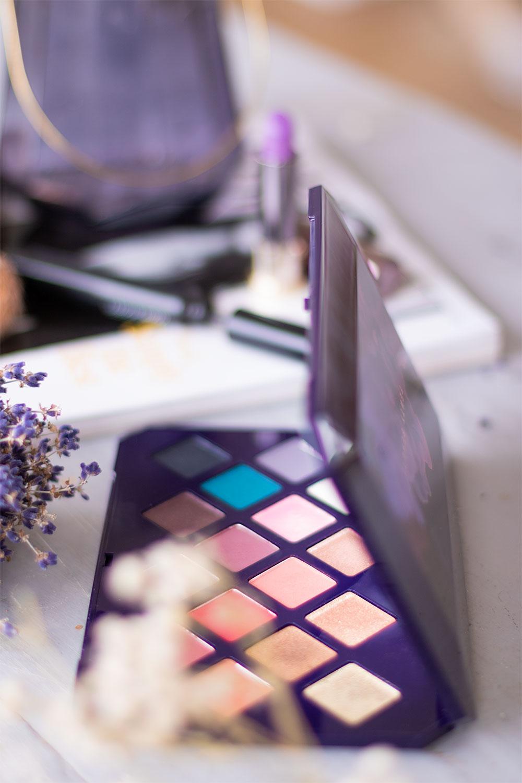 Zoom sur le profil de la palette Moroccan Spice de Fenty Beauty cachée derrière des fleurs séchées blanches, posée sur une table grise en bois devant un magazine
