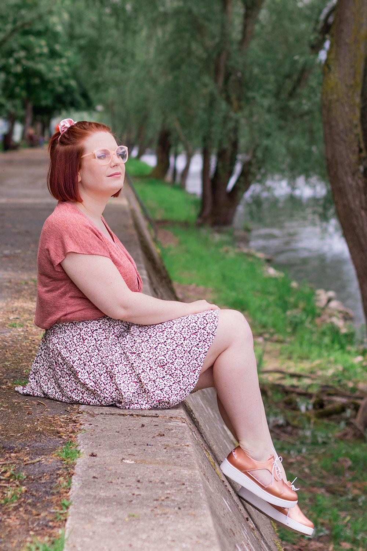 De profil, assise sur les bords de Loire les pieds dans le vide, en jupe fluide et t-shirt rose