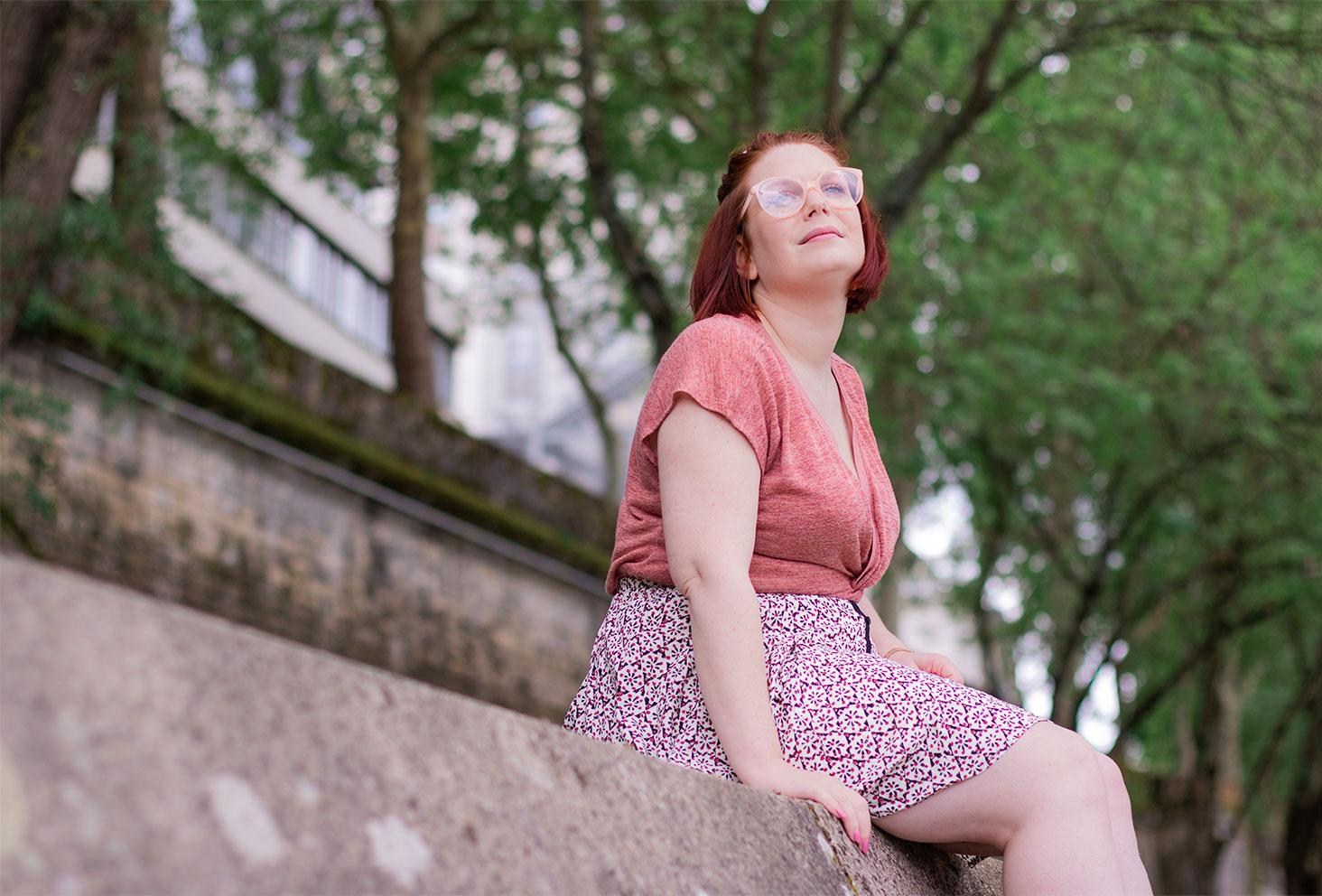 Vue d'en bas, assise sur les bords de la Loire les pieds dans le vide, en t-shirt rose et jupe fluide, le regard dans lointain
