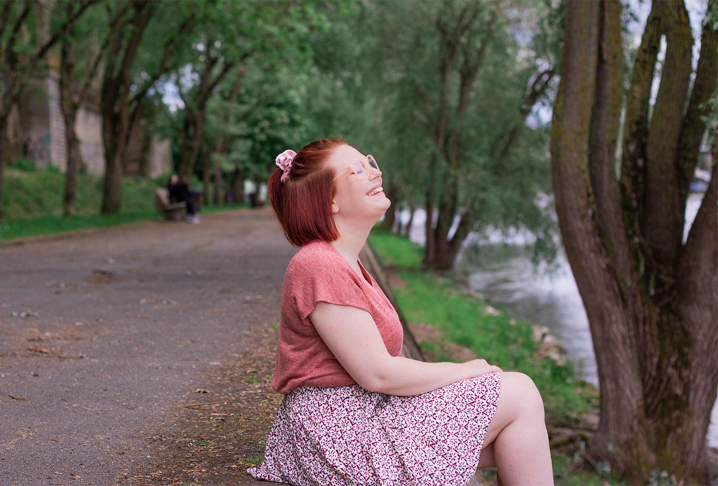 Avec le sourire, de profil assise sur les bords de la Loire, en jupe fleurie