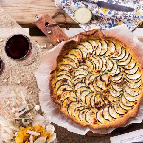 La tarte à la courgette de haut, sur une table en bois au milieu d'un pique-nique champêtre