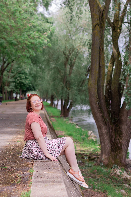 Les pieds dans le vide sur les bords de Loire, assise en jupe fluide, avec le sourire de profil