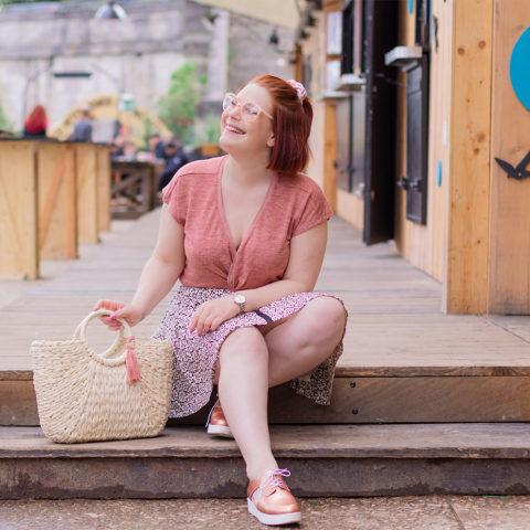 Assise sur l'estrade du bar de la guinguette de Tours avec le sourire, en jupe fluide et top rose, un panier en osier dans la main