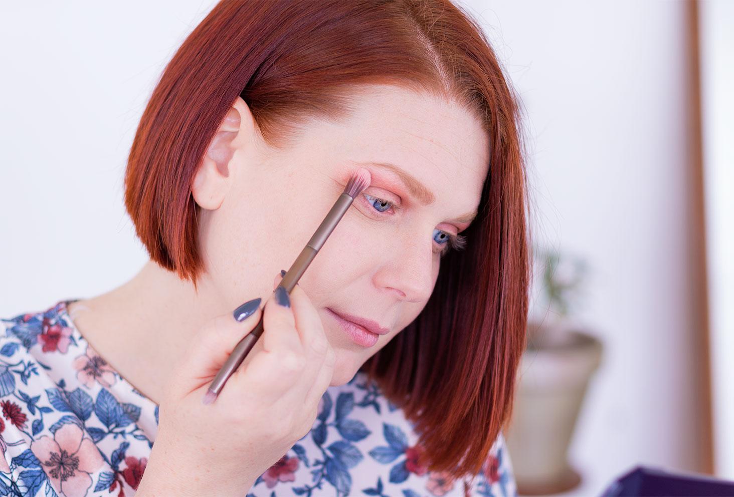 Application du fard orange à l'aide d'un pinceau fluffy lors de la première étape du make-up coloré réalisé avec la palette Moroccan Spice de Fenty Beauty