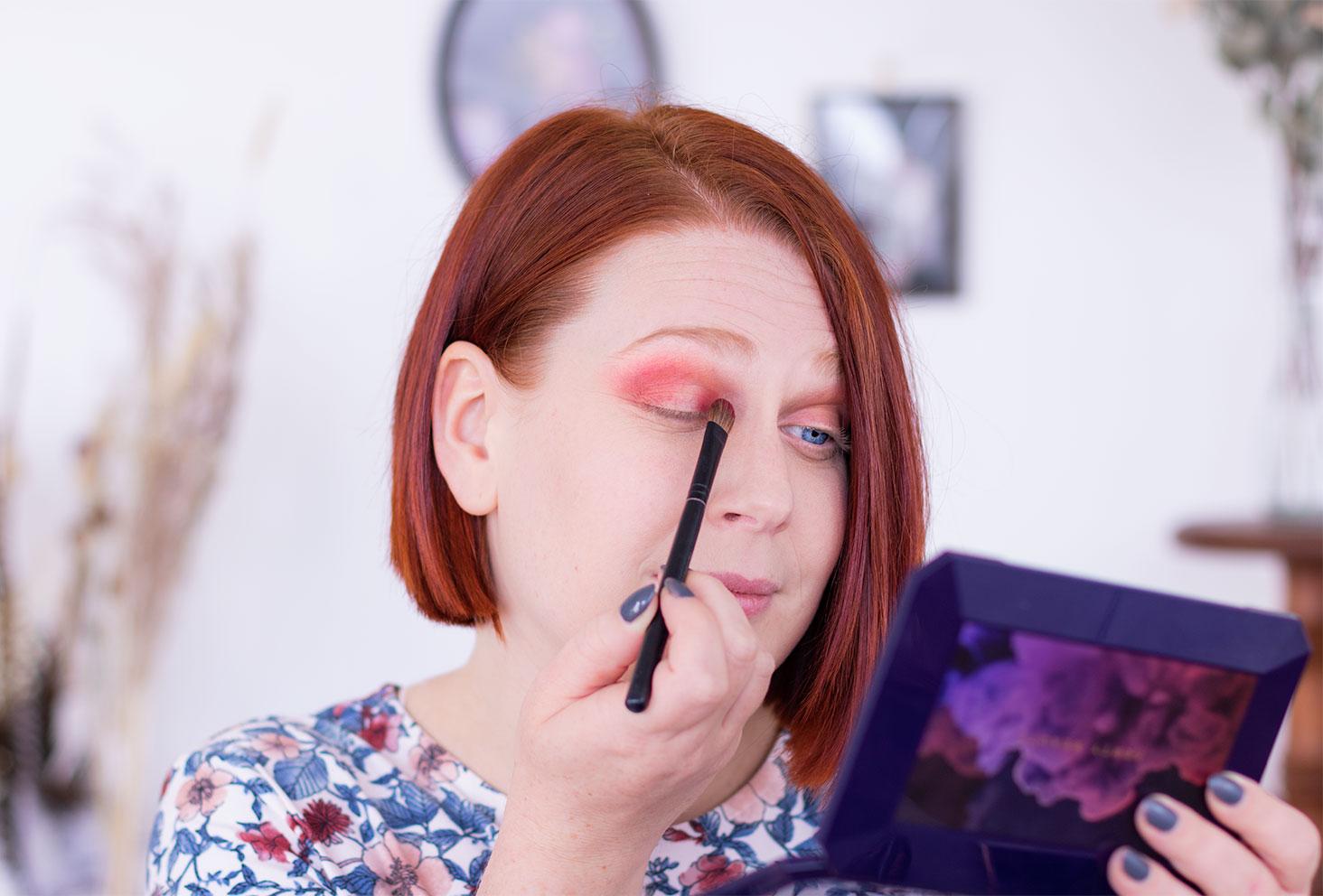 Application du fard rouge à l'aide d'un pinceau fluffy lors de la deuxième étape du make-up coloré réalisé avec la palette Moroccan Spice de Fenty Beauty