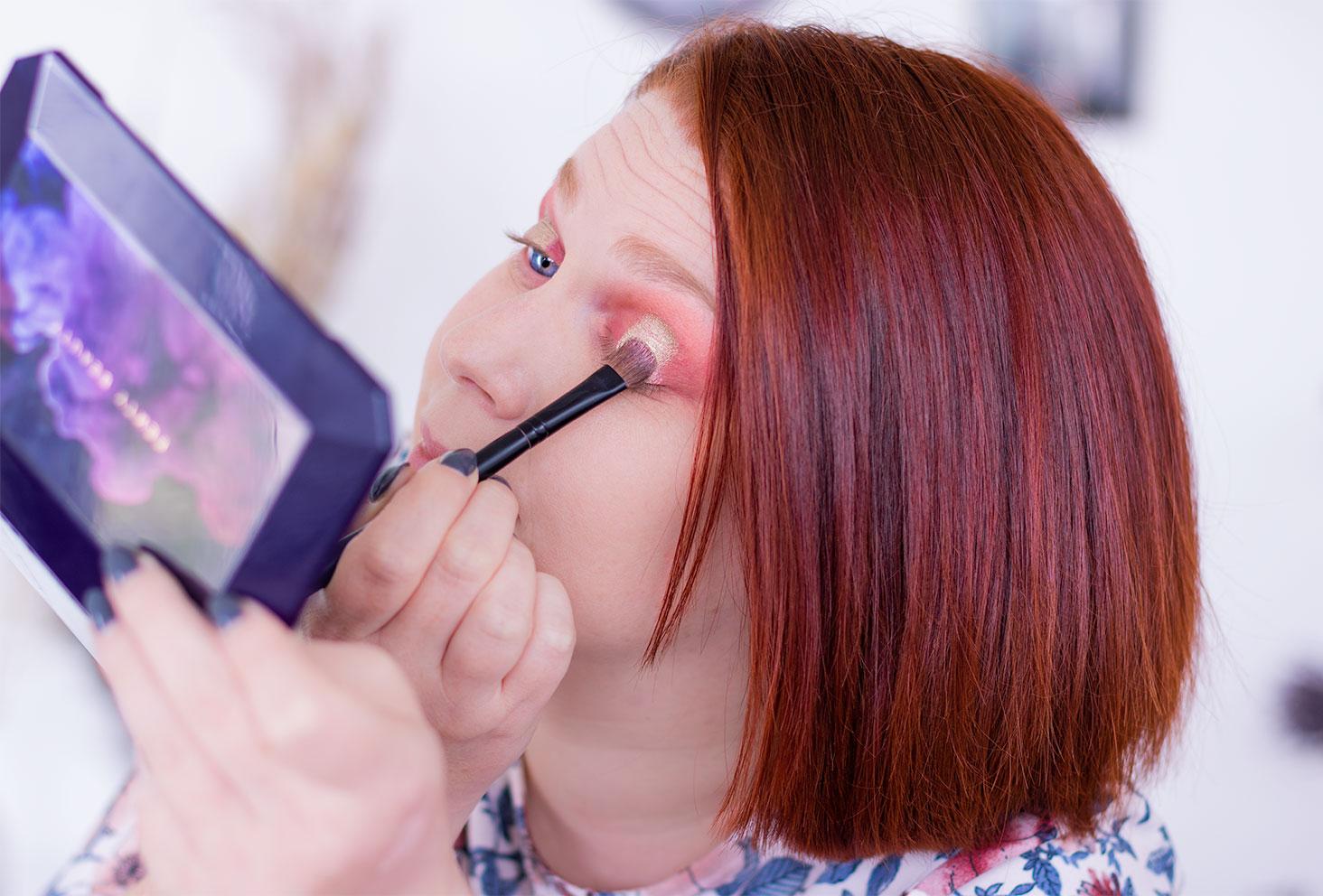 Application du fard doré à l'aide d'un pinceau lors de la troisième étape du make-up coloré réalisé avec la palette Moroccan Spice de Fenty Beauty