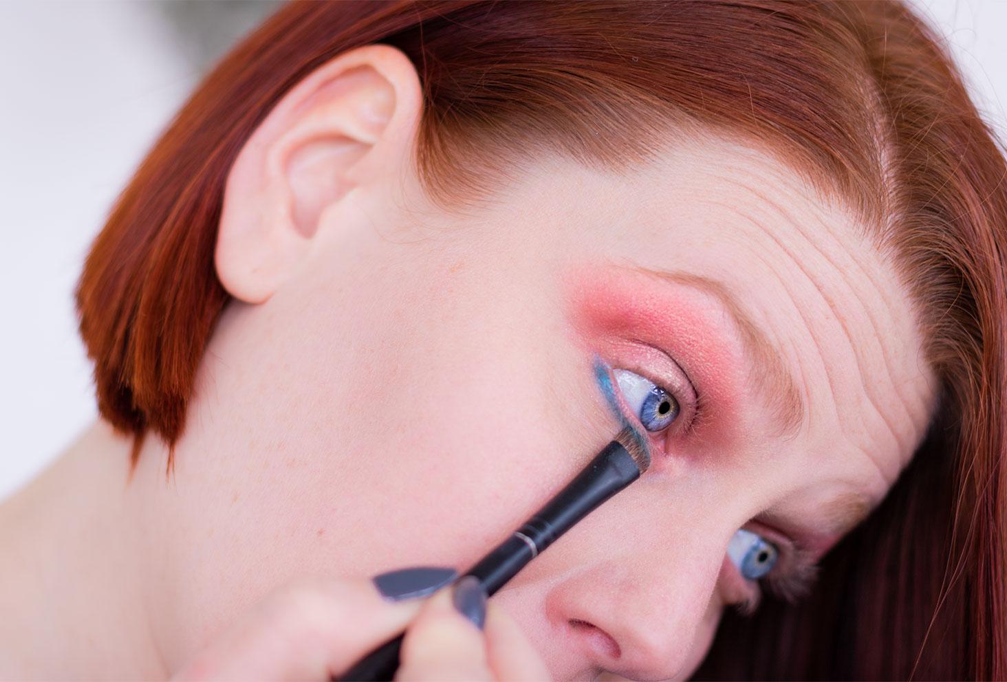 Application du fard bleu en ras de cils inférieur à l'aide d'un pinceau fin lors de la cinquième étape du make-up coloré réalisé avec la palette Moroccan Spice de Fenty Beauty
