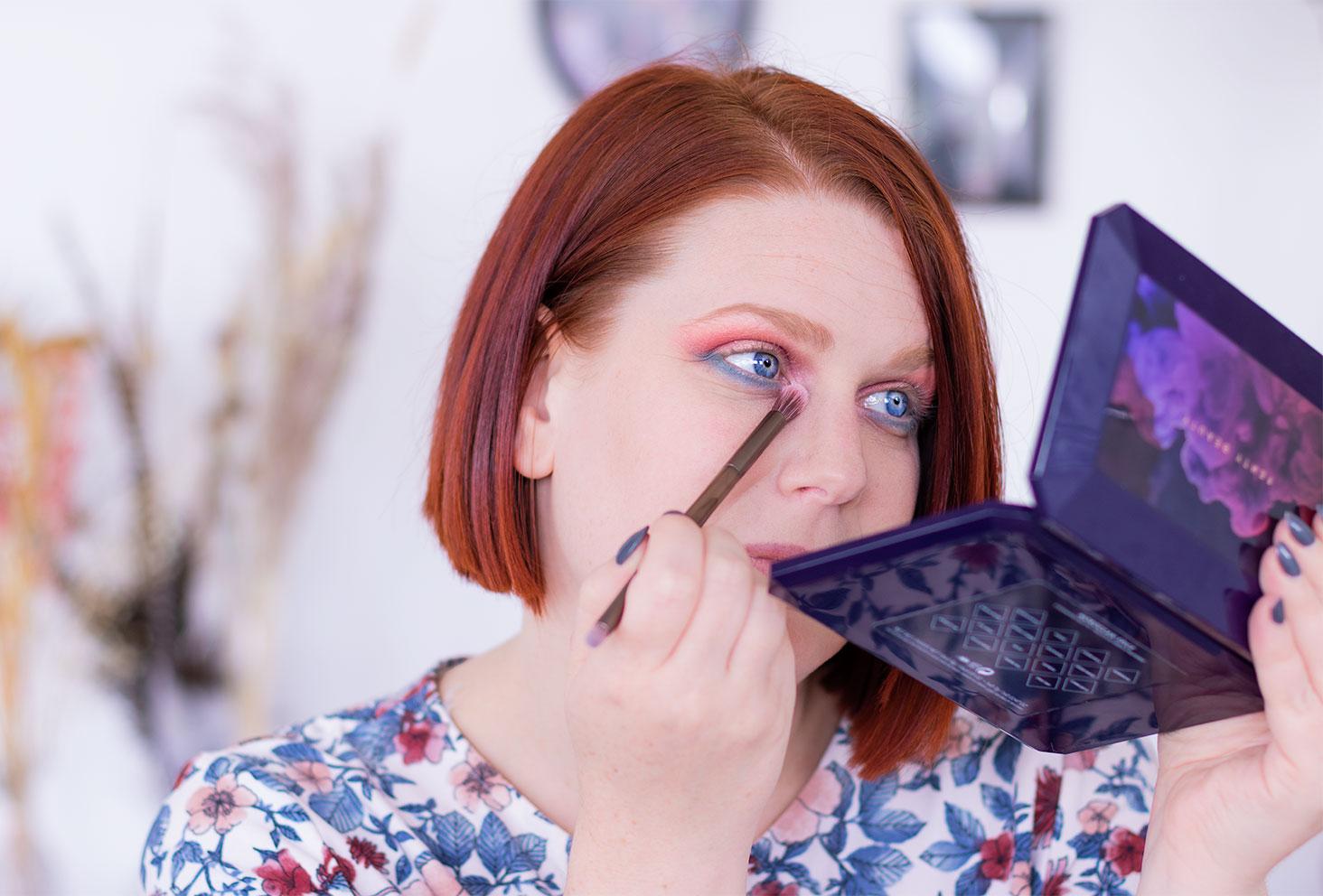 Application du fard blanc à l'aide d'un pinceau fluffy lors de la sixième étape du make-up coloré réalisé avec la palette Moroccan Spice de Fenty Beauty