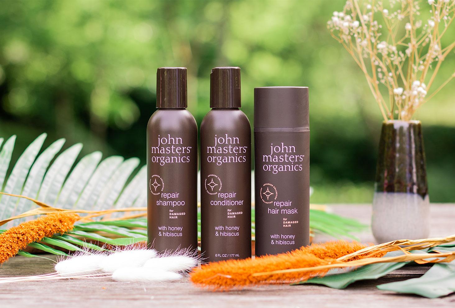 La gamme pour cheveux abîmés de John Masters Organics sur une table en bois entre fleurs séchées et feuilles vertes