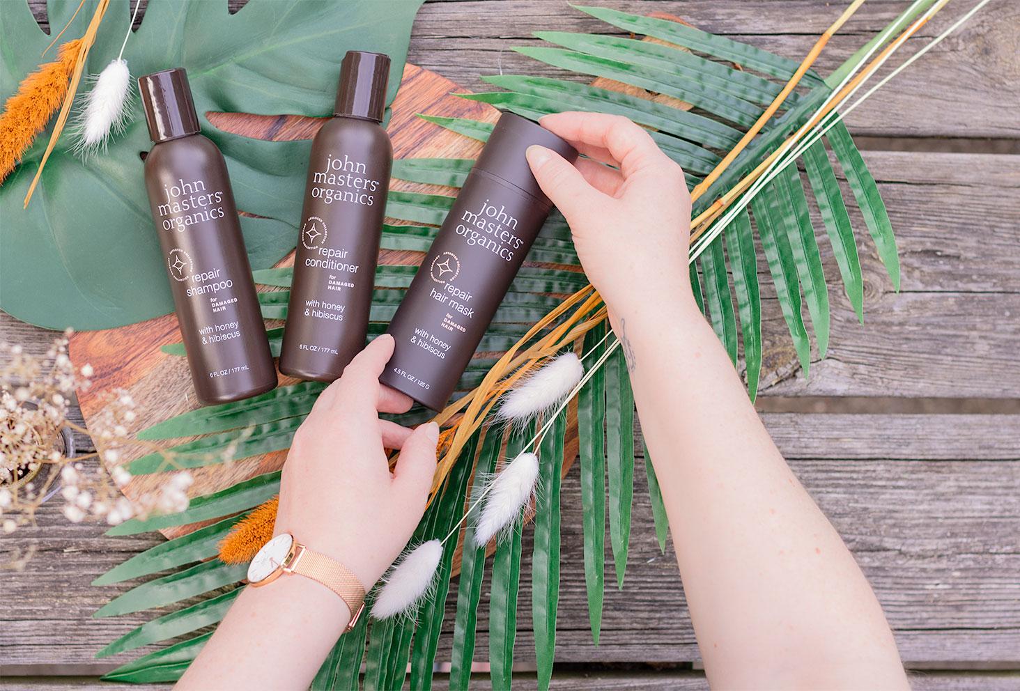 La gamme pour cheveux abîmés au miel et à l'hibiscus de John Masters Organics allongés sur une table en bois, le masque entre les mains, vus de haut au milieu des fleurs séchées