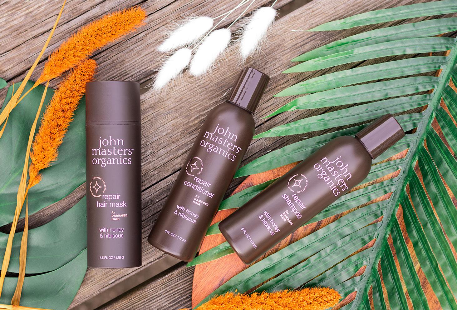 Zoom sur la gamme miel et hibiscus pour les cheveux abîmés de John Masters Organics, vus de haut allongés sur une table en bois au milieu de feuilles de palmier