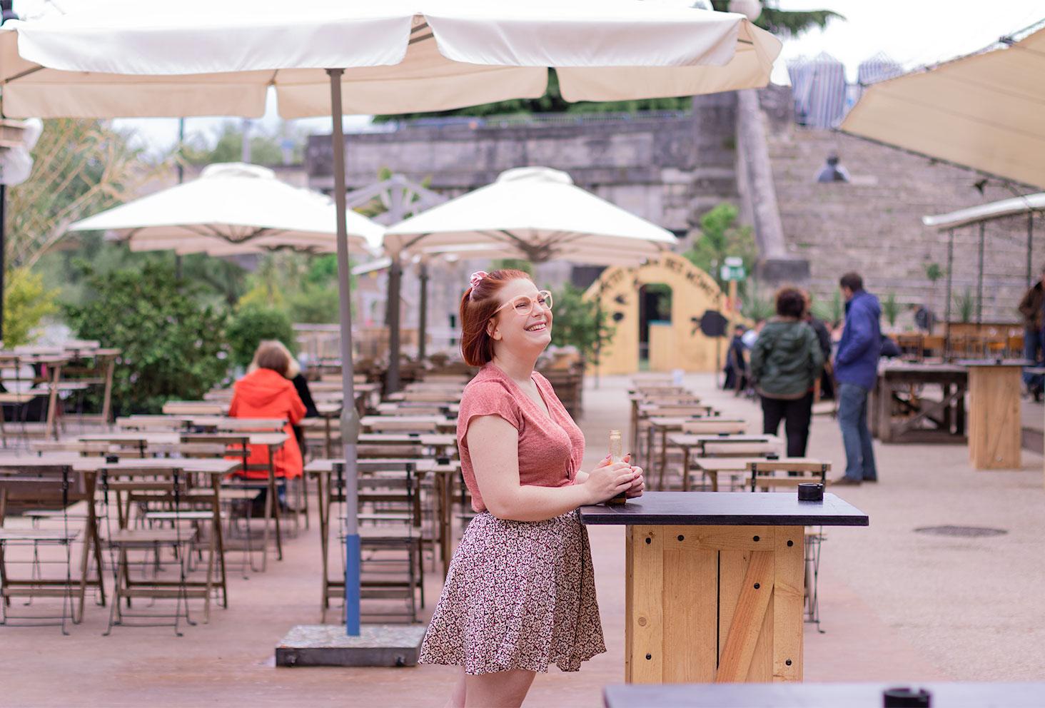 Accoudée à une table de la guinguette de Tours avec une bouteille entre les mains, avec le sourire, en jupe et t-shirt rose