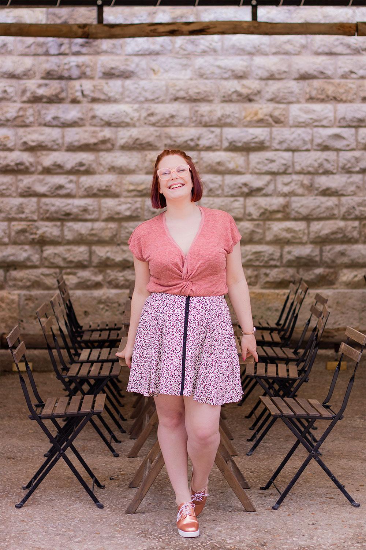Appuyée à une table en bois de la ginguette, en jupe fluide et top rose, le sourire aux lèvres