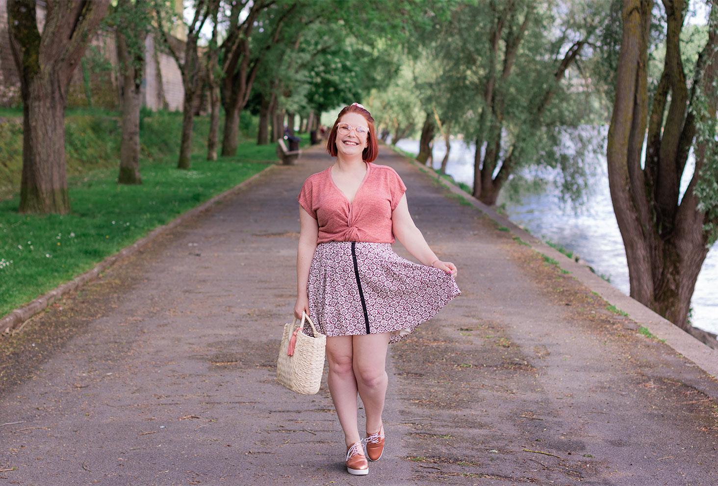 Look rose en entier, jupe fleurie et top fluide, un panier en osier dans la main, avec le sourire sur les bords de Loire de Tours