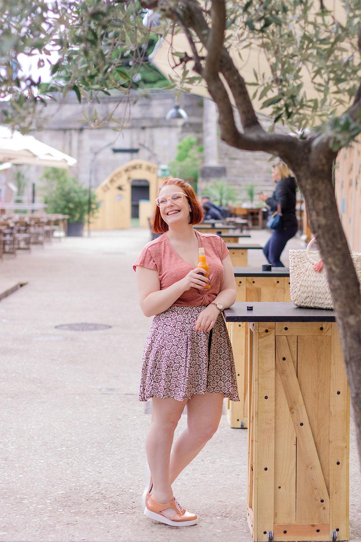 De profil avec une bouteille de jus d'abricot, accoudée à une table de la guinguette de Tours, sous le soleil