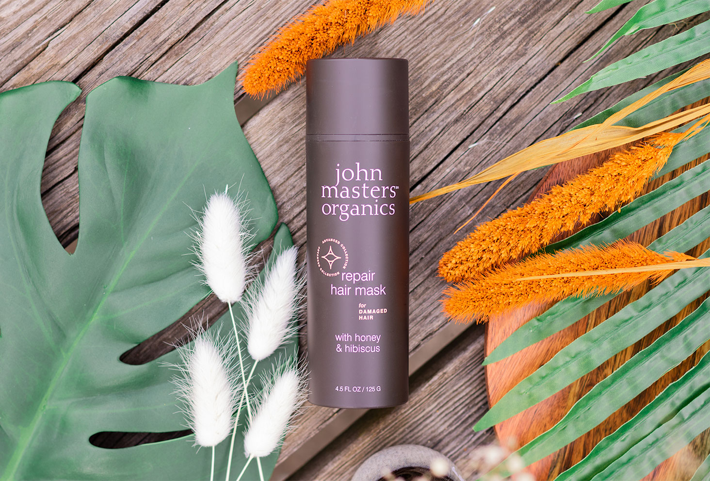 Zoom sur le masque pour cheveux abîmés de John Masters Organics, allongé sur une table en bois au milieu de fleurs séchées orange et blanches