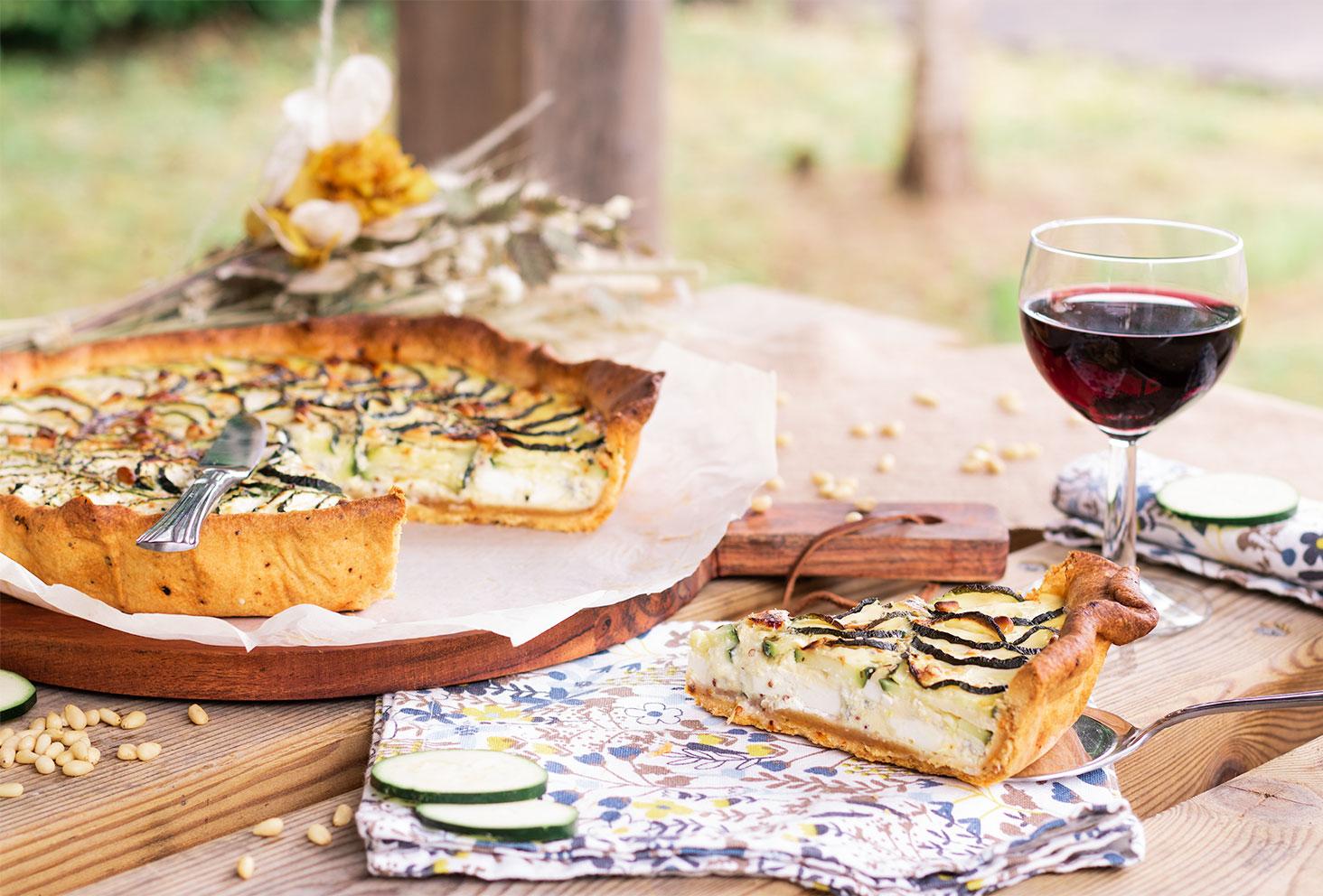 Une part de tarte aux courgettes coupée et posé sur une pelle à tarte, qui est elle même posé sur une serviette en tissu fleurit, au milieu d'un pique-nique champêtre