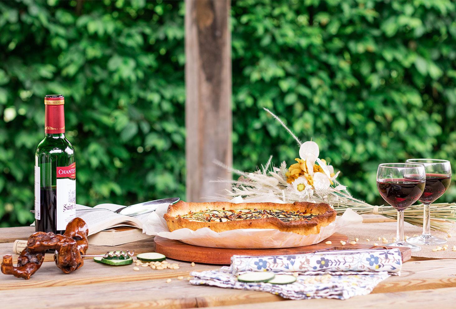 Pique-nique sur une table en bois, avec verres de vin, bouquet de fleurs et tarte à la courgette