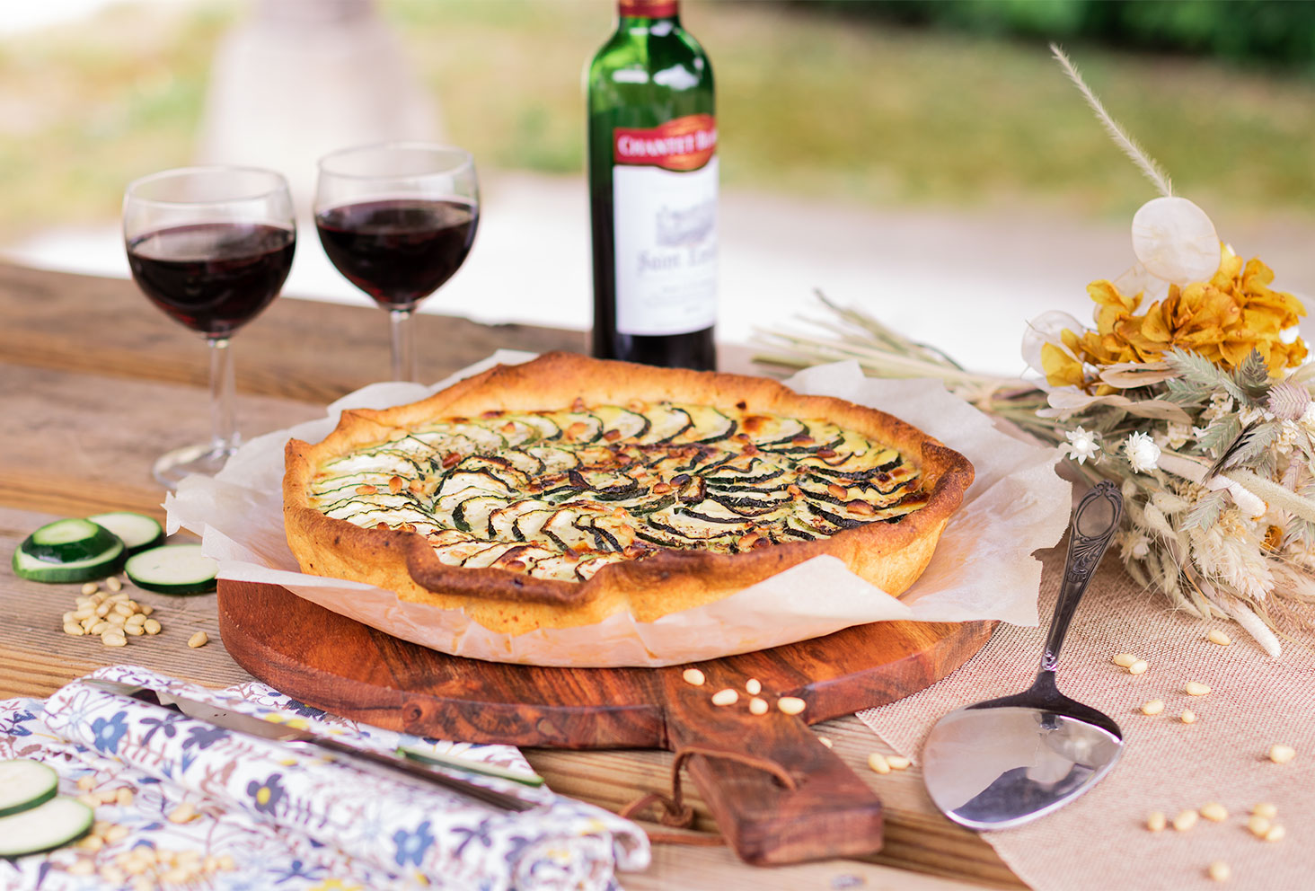 Une tarte courgette posée sur une planche à découper ronde en bois, au milieu d'un pique-nique champêtre