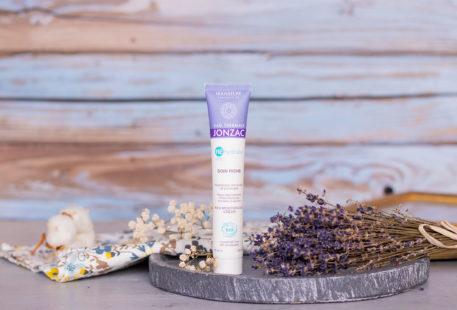 Le tube du soin riche REhydrate de Jonzac sur une plaque d'ardoise au milieu de fleurs séchées violettes et blanches