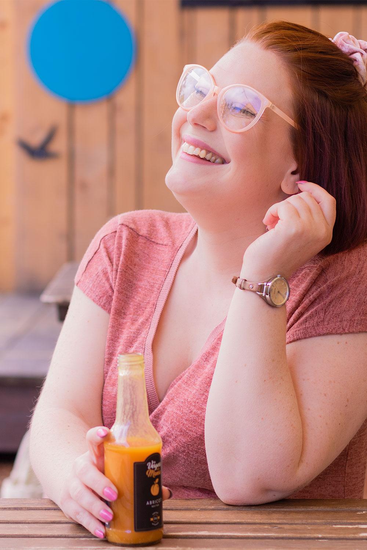 Avec le sourire attablée avec une bouteille de jus d'abricot, une montre Fossil au poignet, de profil des lunettes roses sur le nez