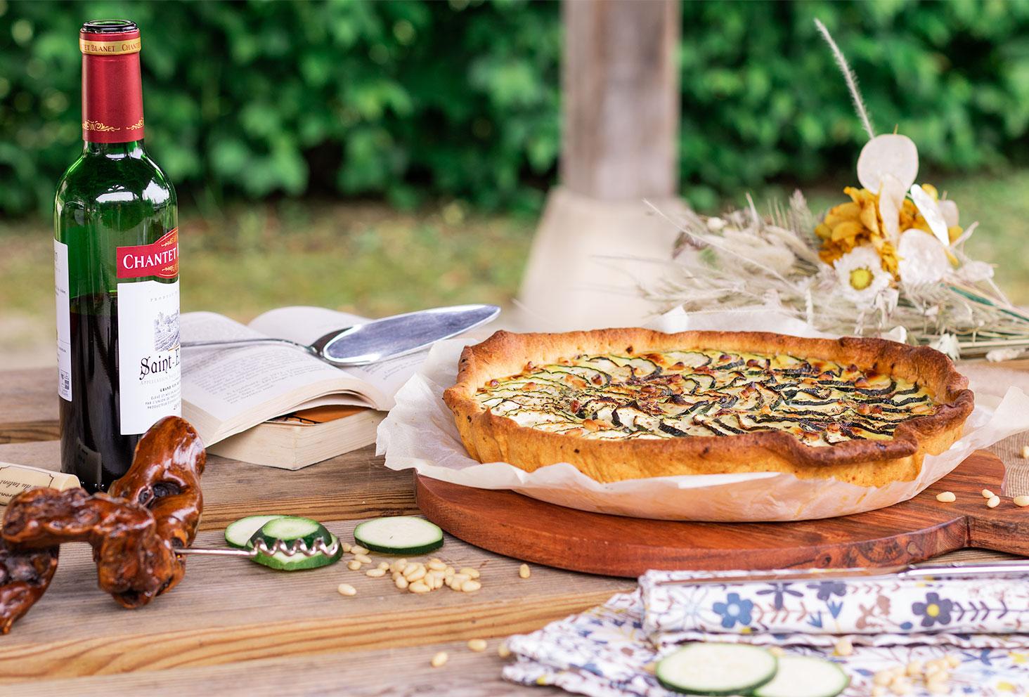 La tarte à la courgette au milieu d'un pique-nique champêtre, posée sur une grande planche à découper