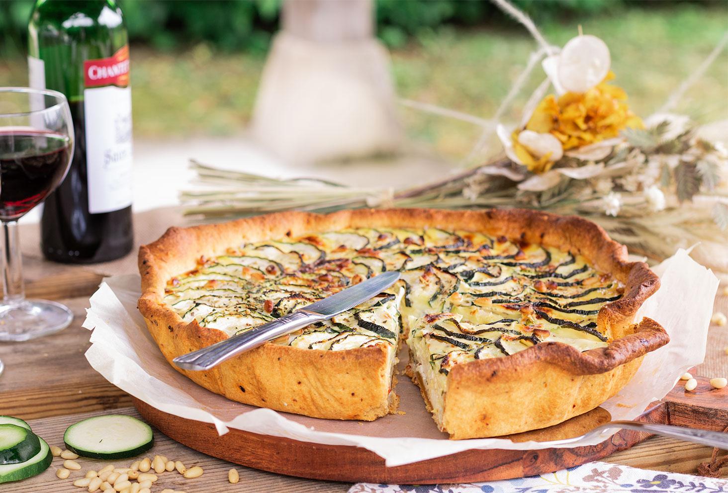 Zoom sur une tarte courgette d'une part coupée, posée sur une table de pique-nique en bois, au milieu de verres de vin et de bouquet de fleurs