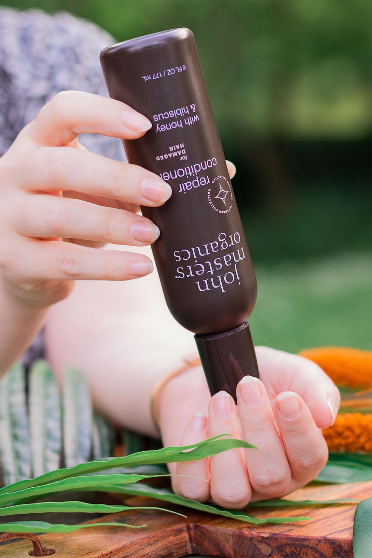 Utilisation entre les mains de l'après-shampoing pour cheveux abîmés de John Masters Organics