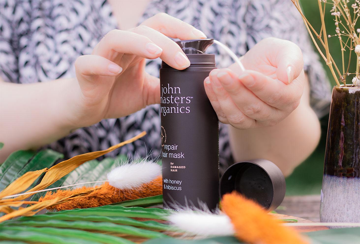 Utilisation entre les mains de la pompe du masque pour cheveux abîmés de John Masters Organics