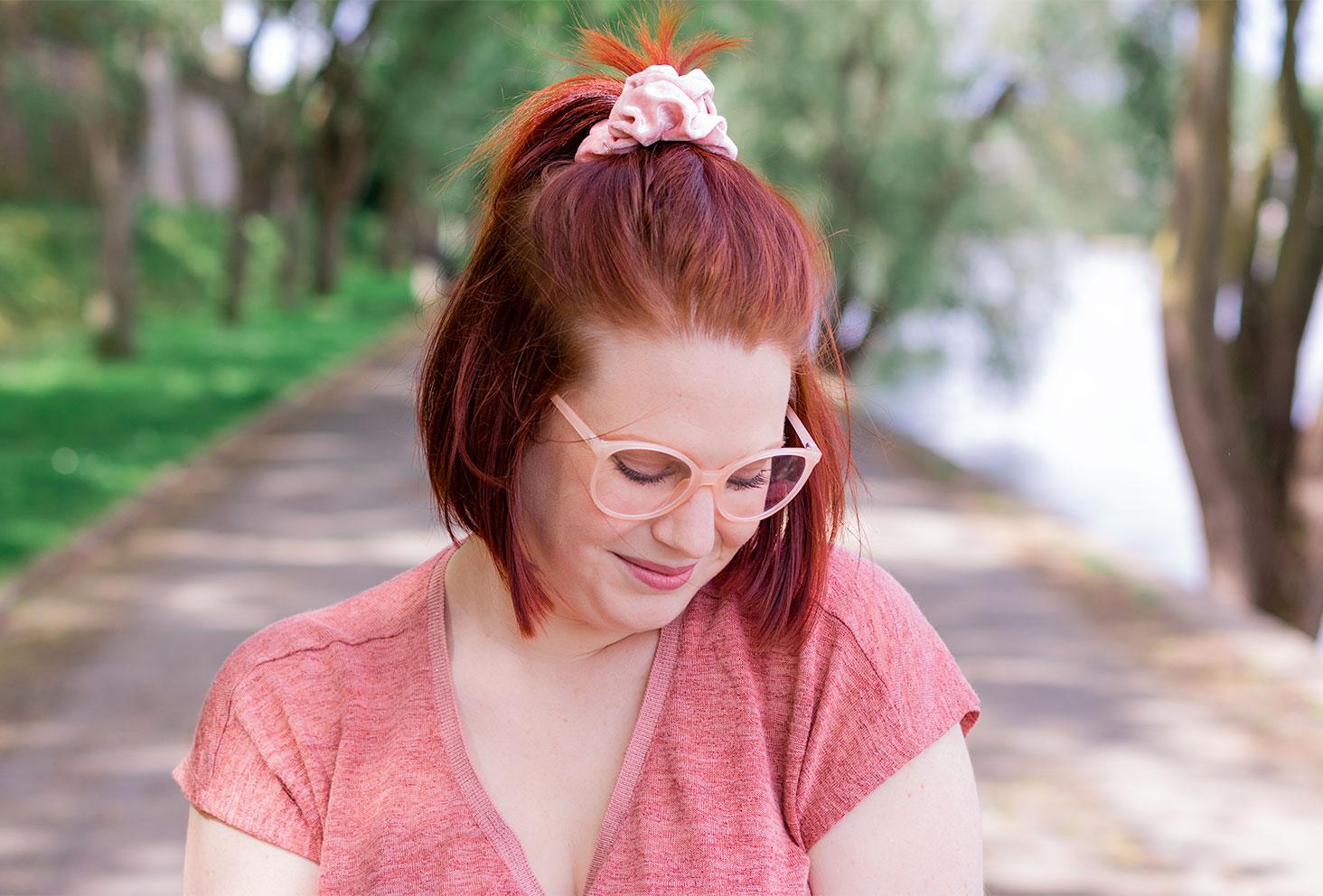 Zoom sur la queue de cheval avec chouchou rose sur le haut de la tête et les lunettes roses sur le nez, sur les bords de Loire