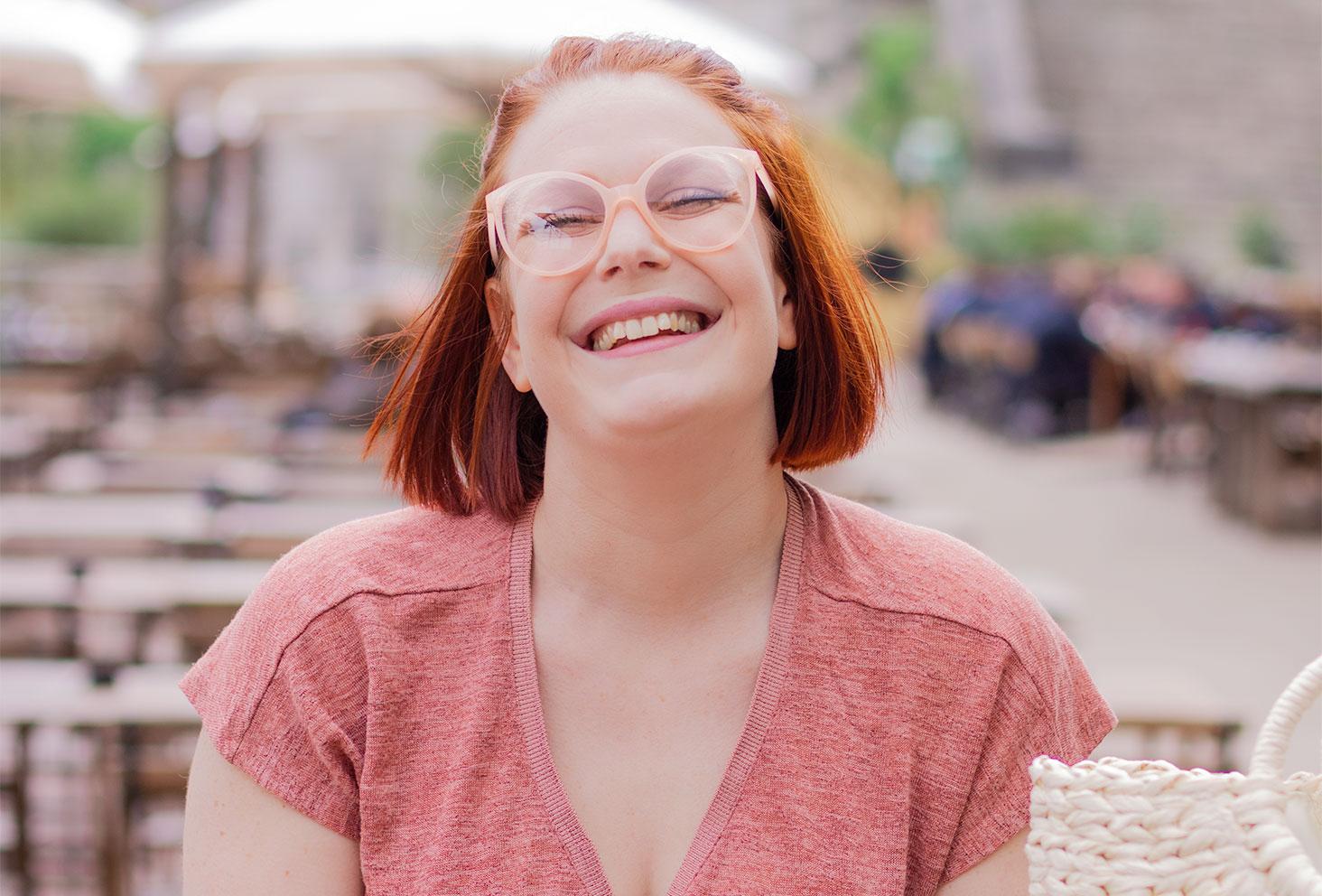 A la guinguette de Tours avec le sourire, portrait avec des lunettes roses poudrées, en t-shirt rose décolleté fluide